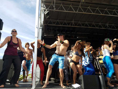 NORTH SHORE, HAWAII - FEBRUARY 26: Guys and Ladies dance with Mike love, Ron Artis II, and Eoin Finn play on stage during Farewell: blissed and blessed yoga class a celebration of the power of yoga, community, music and nature outdoors at Wanderlust yoga