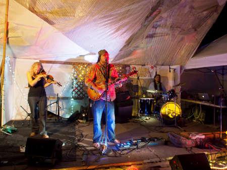 OAHU - 20 FÉVRIER 2017: Le groupe de rock Roxotica, avec guitariste, bassiste, violoniste et batteur à l'Optimysstique 2017 Campout sous une voile géante au Camp Mokuleia sur la côte nord d'Oahu Banque d'images - 79596251