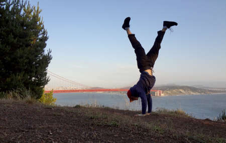 Man wearing hat, hoodie, long pants and shoes Handstands in on hill in front of the Golden Gate Bridge on the Marin side with San Francisco, California in the distance.