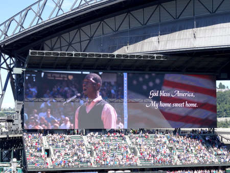 SEATTLE - JUNE 26: Man sings God Bless America on digital screen during baseball game at Safeco Field, Seattle in June 26, 2016.