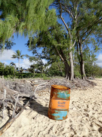 Waimanalo - July 11, 2016: Wash-up Gulf Marine Oil Barrel sits on Waimanalo Beach on Oahu, Hawaii with ironwood trees in the brackground.