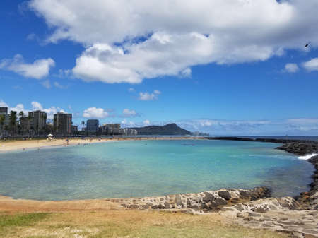 Beach on Magic Island in Ala Moana Beach Park on the island of Oahu, Hawaii.  Waikiki and Diamond Head in the distance and helicopter in the air on a beautiful day. Stock Photo