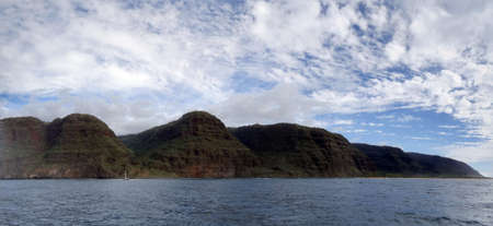 Panoramic of Beautiful Na Pali Coast with clouds in the air and boat in the water as seen from off shore boat.