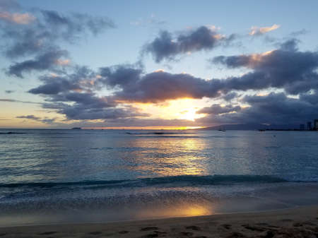 Dramatic Sunset over the clouds and reflecting on the Pacific ocean with boats on the water on Waikiki beach on Oahu, Hawaii with Waianae Mountain range visible.