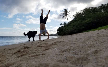 Man Handstands on beach with black dog next to him as wave roll on to shore in Hawaii Kai on Oahu, Hawaii.