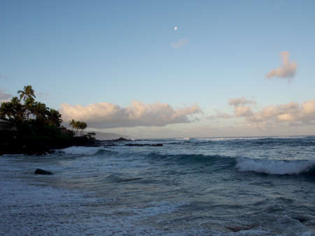 Beautiful Dawn over the ocean with waves crashing into rocks along beach with moon in the sky on the North Shore of Oahu.