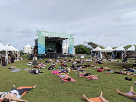 North Shore, Oahu - March 4, 2018: People rest in corpse pose at Catch the Vision outdoor yoga class with Chelsey Korus and DJ Drez at Wanderlust yoga event on the North Shore, Hawaii. Éditoriale