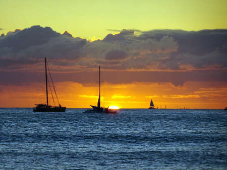 Boats on the pacific ocean waters of Waikiki at Sunset on Oahu, Hawaii.