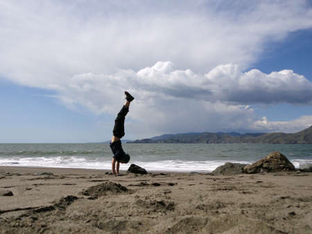 Man wearing a black sweatshirt, beanie, pants, and shoes Handstands on Beach in San Francisco, California.