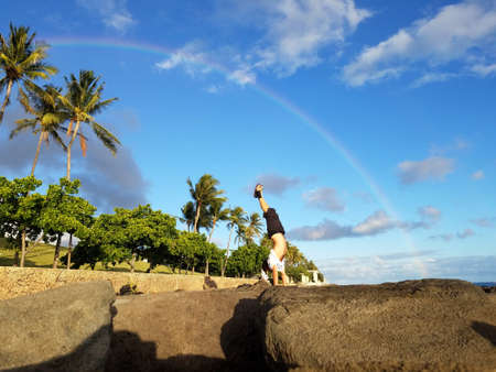 Man Handstanding on coastal rocks with Rainbow overhead and coconut trees along path on Oahu, Hawaii.
