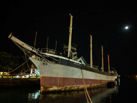 Historic Falls of Clyde Ship sits in Honolulu Harbor at Night with moon in sky. Falls of Clyde is the last surviving iron-hulled, four-masted full rigged ship, and the only remaining sail-driven oil tanker. Editorial