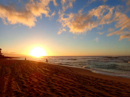 Beautiful Sunset over the ocean with waves moving to shore Sunset Beach on the North Shore of Oahu.     版權商用圖片
