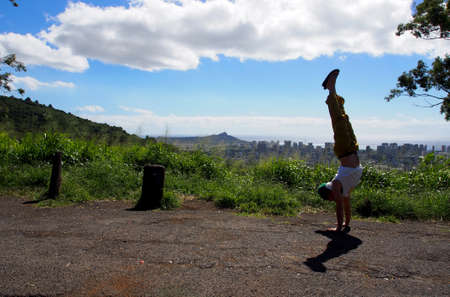Man wearing t-shirt, pants and rubber slippers Handstands at Tantalus lookout point with the city of Honolulu, Hawaii and ocean visible in the distance.
