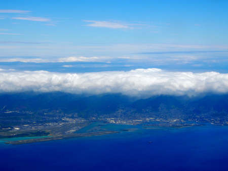 Honolulu International Airport Coral Runway and City seen from the air with surrounding water on Oahu, Hawaii and clouds over the island.  Taken on April 7, 2018.