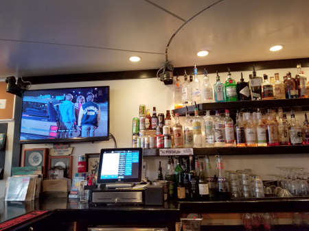 Honolulu - August 6, 2017: Movie plays on TV inside Local Downbeat Diner Bar with liquor on display and cash registrar visible. Редакционное