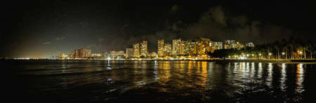 City Lights light up Waikiki and water at Night.  Panoramic view.