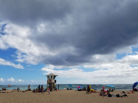 Honolulu - May 20, 2017: People hang out at beach with wavy water on ocean off Kaimana Beach with lifeguard tower on Oahu, Hawaii.