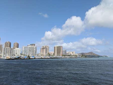 Waikiki - June 9, 2018: Skyline of Waikiki and Diamond Head during day with yachts and boats in Ala Moana harbor, Hotels, Crane, and Hilton Hawaiian Village framing Diamond Head in Waikiki, Oahu, Hawaii.