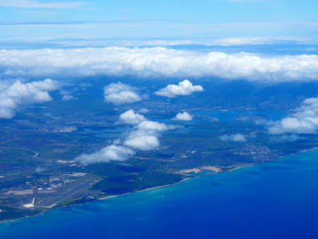 Aerial of Pearl Harbor, Keku Point, and Airport from the ocean with clouds over the island of Oahu, Hawaii.