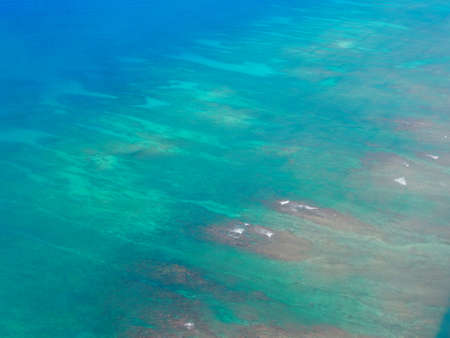 Aerial of Waves lap on reef on coast Oahu, Hawaii into the Pacific Ocean.