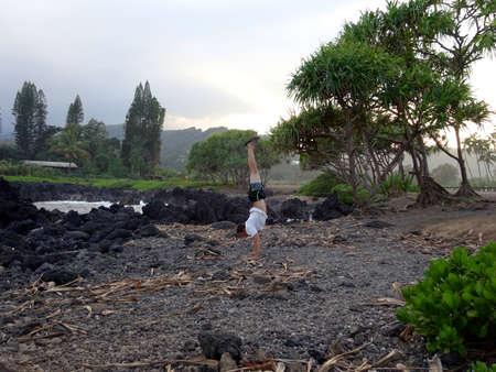 Man Handstands on Rocky shore at Kainalimu Bay on Maui, Hawaii. Stock Photo