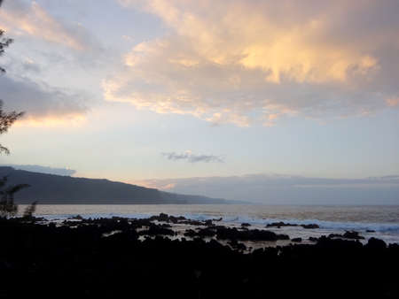 Dusk Along Rocky Shore with waves rolling in and clouds in the sky on Maui, Hawaii. 写真素材