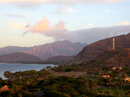 Ko Olina and the Waianae Coast with Mountains in the background, and historic smoke stack on the hilltop at dawn on Oahu, Hawaii.