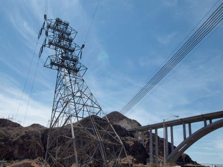 High Voltage Power Lines intersect at a large metal Utility poles by the hoover dam and bridge against a blue sky with clouds. Banco de Imagens