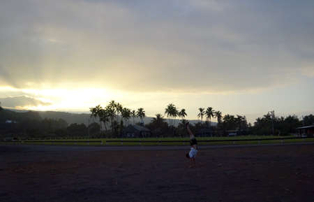 Man Handstands by Baseball & Athletic Field, and church at KeAnae on Maui, Hawaii.
