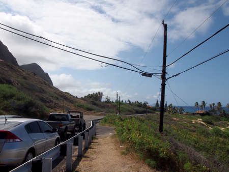 Cars parked along cliffside mountain highway at Makapuu with stretching blue pacific ocean in the distance on Oahu, Hawaii. 免版税图像