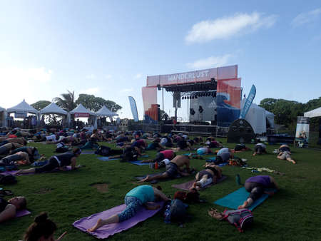 North Shore, Hawaii on February 26, 2016: People do Pigeon Pose during outdoor yoga class facing stage at Wanderlust yoga even.