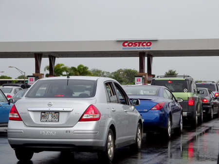 Maui - January 25, 2015:  Cars line up for Costco Gasoline. Costco Gasoline Significantly reduces harmful pre-existing deposit buildup on critical engine components. Restores fuel economy. Protects fuel injectors and intake valves from harmful deposits.