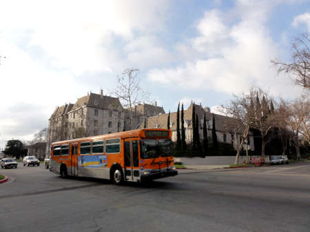 LA - Febuary 15, 2011: Orange Local Metro Bus 14 rolls down the street in front of the Faubourg St Denis building. Editorial