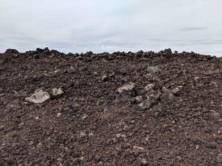 Mountain of Lava Rocks and cloudy sky in Kaloko-Honokōhau National Historical Park on Big Island, Hawaii.