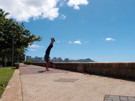 Man Handstands along pathway of Kewalo Basin Park with Waikiki, and Diamond Head in the distance on Oahu, Hawaii on a beautiful day.