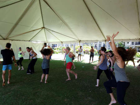 North Shore, Hawaii - February 26, 2017: People dance outdoor under a tent during Ecstatic meditation dancing class at Wanderlust yoga event. 新聞圖片