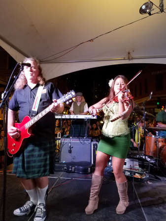 Honolulu -  March 17, 2017:  Wendi Mayhugh plays violin as Band plays on stage at St. Patricks Day Block Party in street in Chinatown.