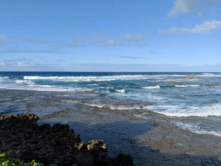 Waves break over rocks at Kuilima Cove at Turtle Bay, Oahu Island North Shore, Hawaii.