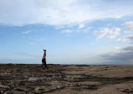 Man wearing a t-shirt, shorts, and slippers Handstands on shore rocks of Ko Olina on Oahu, Hawaii with dramatic clouds, sky, and pacific ocean in the distance.