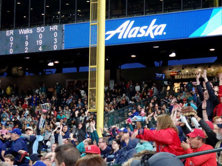 SEATTLE - JUNE 24: Fans in bleachers do the wave with scoreboard above featuring Alaska Airlines ad at Safeco Field during baseball game, Seattle in June 24, 2016.