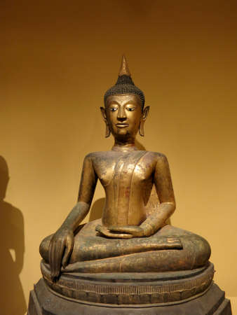 HonoluIu - May 9, 2015: Seated Buddha, 16th century, Artist is Anonymous, Medium Gilt bronze, inlaid shell and black lacquer, Geography: Thailand.  Displayed at Honolulu Museum of Art.