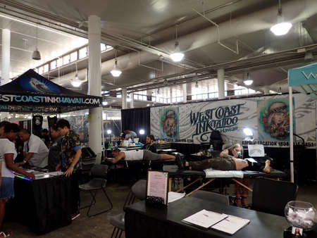 Honolulu - August 6, 2017: People lays on tables as they get tattoo from men at the Hawaii Tattoo Expo. Imagens - 133369136