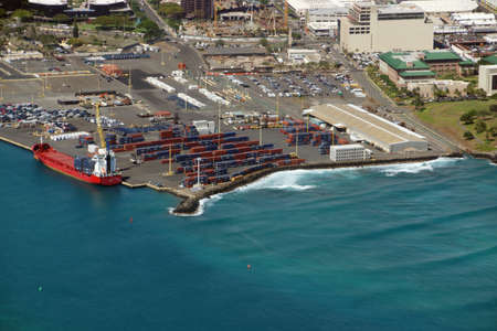 Honolulu - June 26, 2015: Aerial of Cargo Boat being unloaded on Pier 1, Re-Use Hawaii, Medical College, and Water Treatment Plant along the coast at the harbor entrance of Oahu, Hawaii.