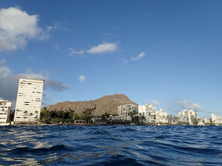 Hotel building, Outrigger Canoe Club, coconut trees, Condo buildings, clouds, and Diamond Head Crater in the distance on Oahu, Hawaii viewed from the water on a beautiful day.