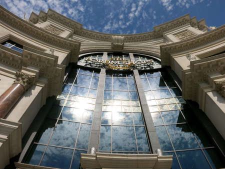 Las Vegas, Nevada - June 29, 2015: The Forum Shops sign and blue sky; mall connected to Caesars Palace; extension wing of main casino; simulates ancient Roman streets including fountains, statues and facades during the day.