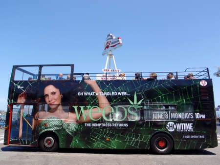 San Francisco  - July 9, 2009: Tour Bus with Weeds Showtime TV Show ad on side and  Ferry Terminal in the background in California. Redactioneel