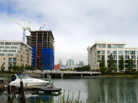 San Francisco - July 24, 2007: Mission Creek waterway with houseboats, Condo under construction, and modern buildings on a foggy day. 報道画像