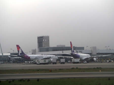 Seattle - May 17, 2019:  Hawaiian Airlines Planes parked at Seattle–Tacoma International Airport terminal in the Fog. 新聞圖片