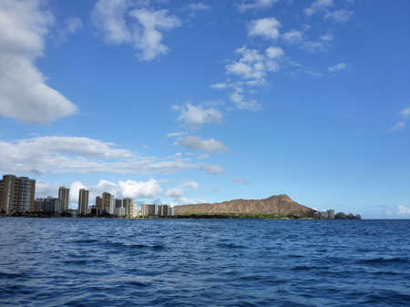 Hotel building, coconut trees, Condo buildings, clouds, and Diamond Head Crater in the distance on Oahu, Hawaii viewed from the water on a beautiful day.