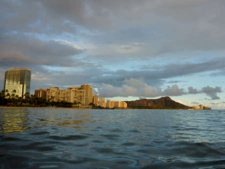 Waikiki Hotel building, clouds, and Diamond Head Crater in the distance on Oahu, Hawaii viewed from the water at dusk on a beautiful day.